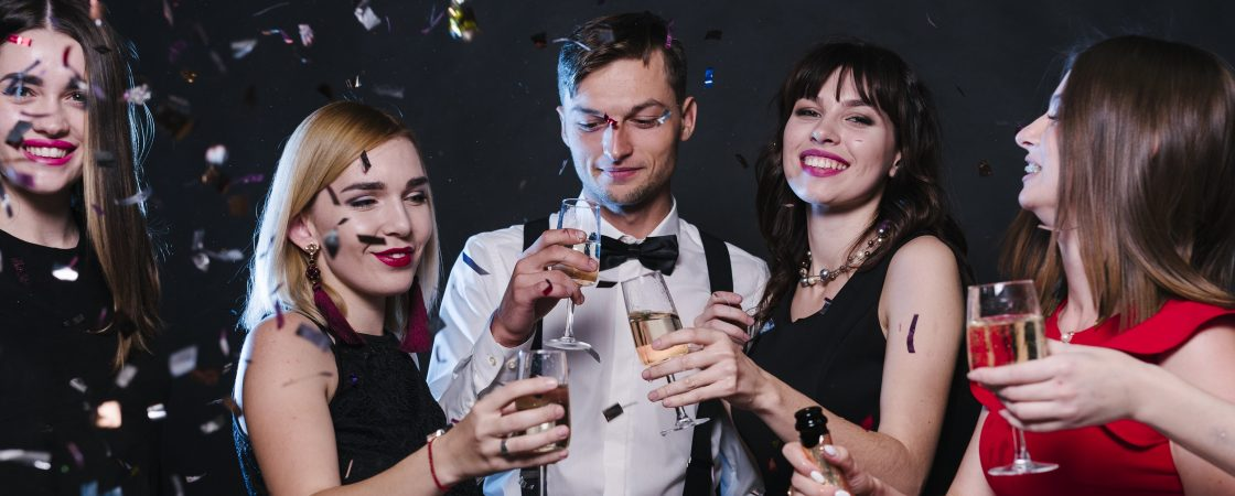Man and two ladies in formal dress at a party