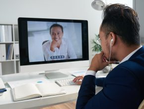 Man sitting at his table and video calling a doctor